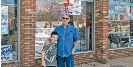 Dennis Saraceni stands with his grandson outside of the family business.
