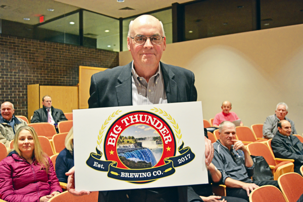 John Robinson, a principal in Big Thunder Brewing Co., holds an artist's rendering of the company's logo during the Wheatfield Town Board meeting.