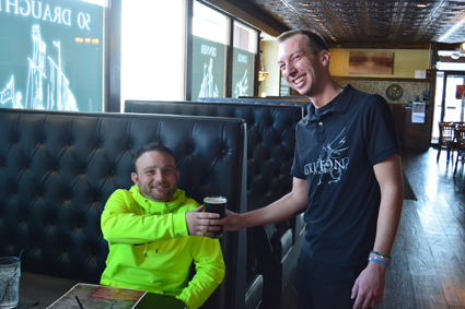 Jordan J. Toohey, right, serves a pint of Fuller's to customer Albert Fiocco of Niagara Falls.