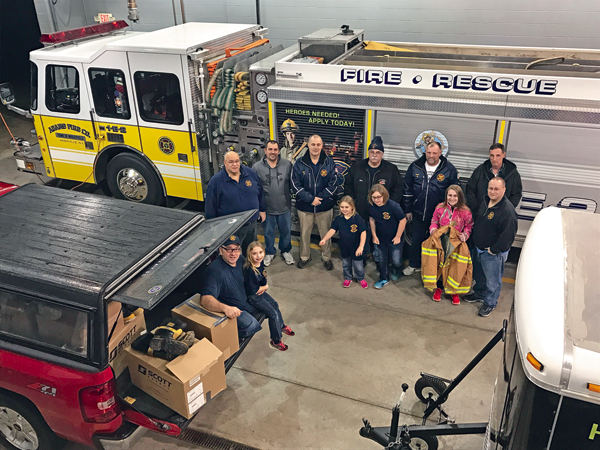 Wheatfield firefighters and family members pose for a photo at Adams Fire Co. after packing donations.