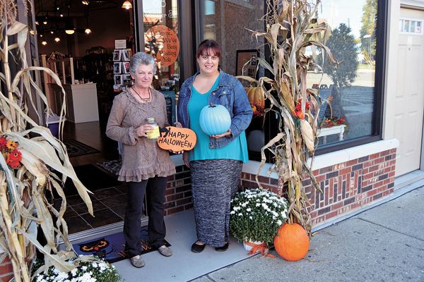 Michele Krienbuhl (left), owner of Michel's Motif on Webster Street, holds a jar ready to accept donations for Twin Cities Meals on Wheels at the first `Boutique Bash.` Jars will be placed at each participating business during the event. Heather Kalisiak holds her teal pumpkin that she will place in her business's window (Martinsville Soapworks) during the trick-or-treat event and `Haunted Sidewalk Sale` to raise awareness about children's food allergies.