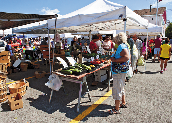 Shown are shoppers browsing goods at the North Tonawanda Farmers Market, on the corner of Payne Avenue and Robinson Street. The Town of Niagara Farmers Market will be set up in a similar fashion, and will run each Sunday beginning May 8. The North Tonawanda market will open on Memorial Day weekend and run 7 a.m. to 1 p.m. every Tuesday-Thursday and Saturday. (File photo)