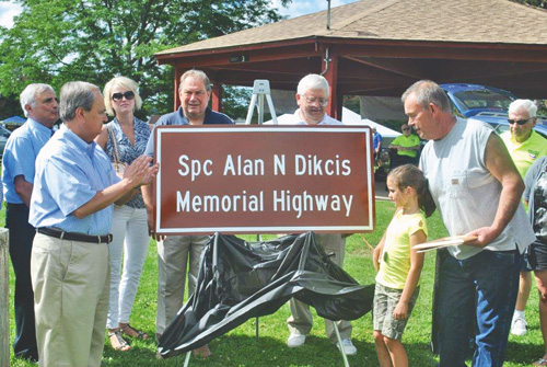 Local officials gather around as Spec. Alan N. Dikcis' daughter, Sophia Brown, and father Bob Dikcis unveil the memorial sign. (photo by Walt Bissett).