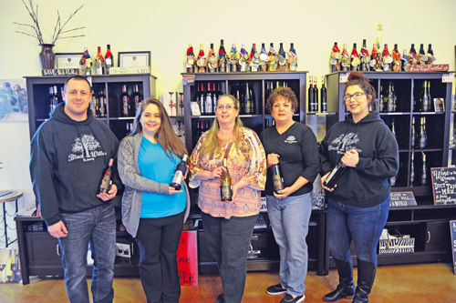 Black Willow Winery staffers display a variety of wines. From left are staff members Jonathan Little, Amanda Mitchell, owner Cynthia West-Chamberlain and staff members Rebecca Scott and Brianna Beane.