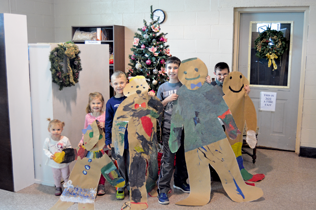 From left: Anaston, Payton and Dexton Tompkins, alongside Will Bartel and Josh Rollian, show off the life-size ginger bread people they created at the YWCA. (Staff photos)