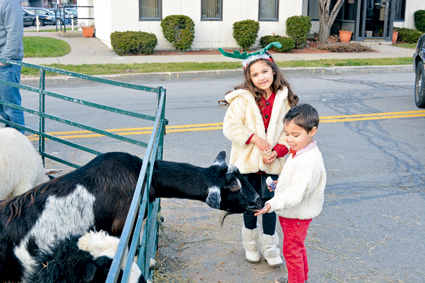 Elise and Owen Rambally help feed the animals at the petting zoo outside the YWCA.