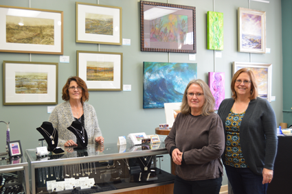 From left: Local artists Dawn M. DiGesare, Susan M. Miller and Deanna Weinholtz stand by their artwork at the River Gallery, where they all volunteer and sell pieces.
