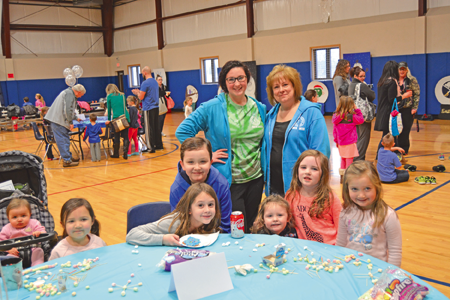 You Center Administrative Assistant Debbie Reed (standing, at right) and Olivia Toner pose for a photo with children at one of the children's activities stations. (Photo by Lauren Zaepfel)
