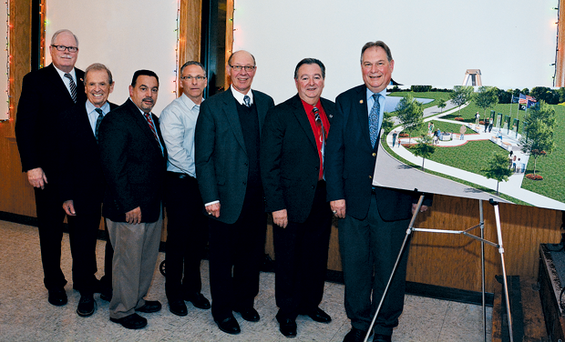Shown are Town of Niagara Supervisor Lee Wallace and community officials with a rendering of the planned Veterans Memorial. (Photo by Marc Carpenter)