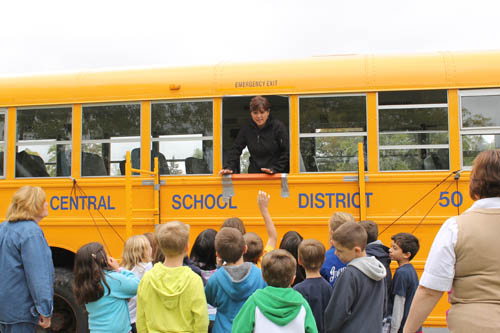 Amy VeRost of the Grand Island Central School District's Transportation Department begins instruction in how to exit a school bus in the event of an emergency. VeRost was part of a team of department personnel who taught students at Huth Road Elementary School safety basics this week. (photo by Larry Austin)