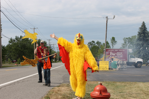 Bob Mesmer and Kyle Huttenmaier helped direct traffic in and out of St. Martin-in-the-Fields Episcopal Church at 2587 Baseline Road during the annual chicken barbecue and basket auction. Mesmer and Huttenmaier had help from Jazzlyn Igiel, in the chicken suit. Tom Igiel, chairman of the event, said it was his daughter's first time in the chicken suit. Jazzlyn said it was the last time as well. (photo by Larry Austin)