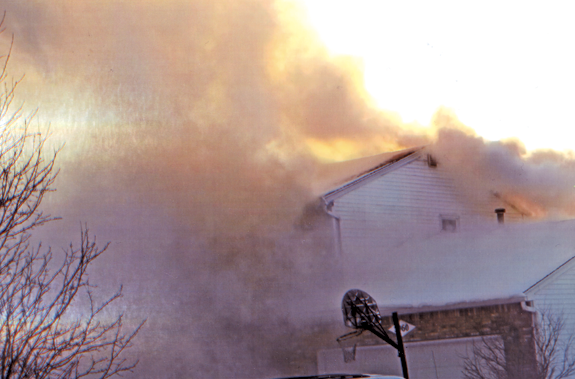 Heavy smoke pours from the roof area as Grand Island Fire Co. units arrive on location to a fire on Baseline Road.