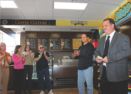 Chuck Rizzo, far right, thanks supporters at the ribbon-cutting for his business, the Dino-Mart gas station and convenience store at the corner of Stony Point and Ransom roads. To Rizzo's right is partner Gino Zagarrio.