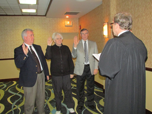 Michael Keating, Dr. Sherry Bradford and Jim Sharpe (pictured at far right) are sworn in by Town Justice Mark Frentzel.
