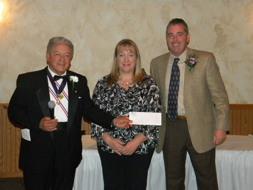 Members of Mary Star of the Sea Council praised Paul Minton for a job well done. Pictured, Grand Knight Rick Gonzalez presenting a gift to Minton and his wife, Mary.