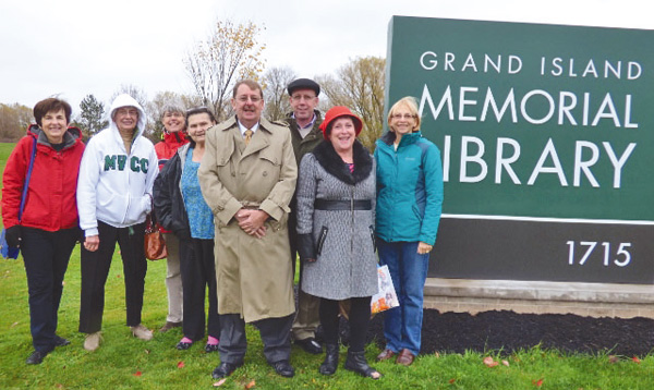 Pictured, from left, in front of the new Grand Island Memorial Library sign are library trustees Pat Rizzuto and Barbara Birt, Friends President Mary Cooke, Sarah Becher, Library Director Lynn Konovitz, Town Board liaison to the library trustees Councilman Richard Crawford, Candy Broman and library trustee and Friends board member Jill Banaszak. (photo by Alice E. Gerard)
