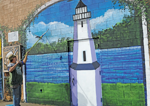 Artist Terry Klaaren puts finishing touches on part of the Grand Island Plaza mural.