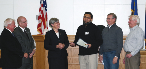 Fahim Mojawalla, media director for the Grand Island Chamber of Commerce, talks about `Small Business Saturday,` Nov. 30, during Monday's Grand Island Town Board meeting. Mojawalla, who also owns the Island Ship Center on Whitehaven Road, accepted a Town Board proclamation on behalf of the chamber along with chamber representatives Jim Sharpe and Skip Mazenauer. From left: Councilmen Gary Roesch and Dick Crawford, Town Supervisor Mary Cooke, Mojawalla, Sharpe and Mazenauer (publisher of the Dispatch). (photo by Larry Austin)