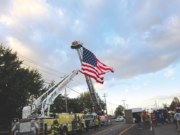 Ladder trucks hang Old Glory over Baseline Road across from the Big House, GIFC fire headquarters. (photo by Colleen Rebmann)
