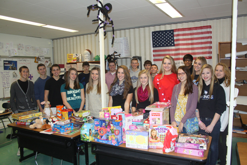Members of Christopher Simpson's second period marketing class at Grand Island High School stand in back of a collection of toys destined for Roswell Park Cancer Institute.