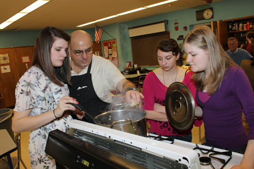 Rotarian Angelo Grande adds ingredients to a pot of soup cooked by Lexie Black, Kate Gilbert and Amanda Blanton. (photo by Larry Austin)