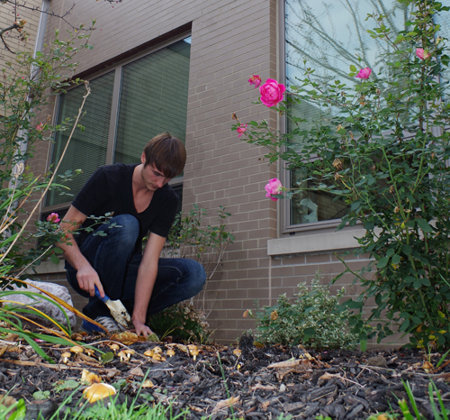Chris Komin plants some bulbs in the garden of the Grand Island High School library courtyard on Oct. 26. Komin, co-president of the Interact Club, and other club members planted 53 bulbs after school. See Page 20 for a group photo of some of the Interact volunteers. (photo by Larry Austin)