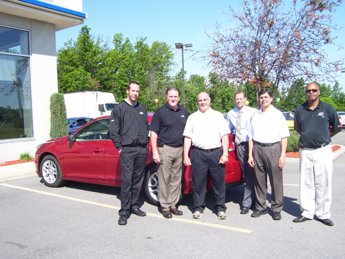 Island Happenings silver sponsor Tom Kanaley and his team at Fuccillo Chevrolet pose next to one of the new cars available at the Fuccillo Chevrolet dealership.