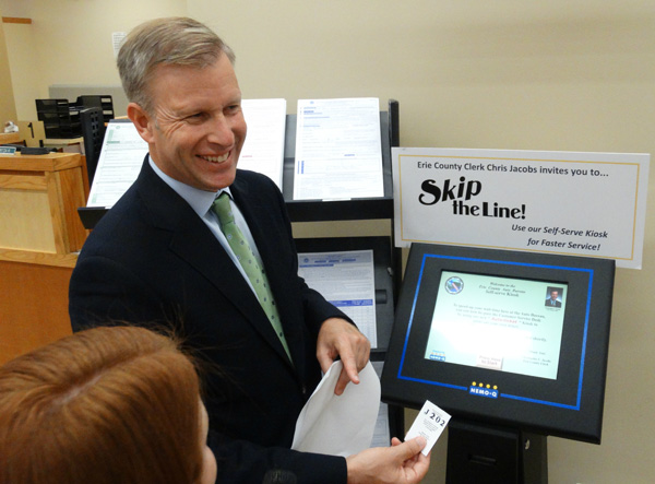 Erie County Clerk Chris Jacobs demonstrates to customers how to use the new online reservation system at the Erie County Auto Bureau.
