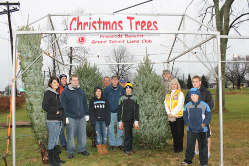 New Christmas trees arrived at Kelly's Country Store on Wednesday. There to help set up their display were, from left, Christina Podlucky of Grand Island High School; Sean Kelly, owner/president, Kelly's Country Store; GIHS students Donald Faling and Brittanee Ramallo; Brian Grim of Kelly's Country Store; Grand Island Lions Treasurer Dick Crawford and Director Mike Steinagel; Jack Steinagel, Lions Club Past President Dave Chervinsky, Lions Club President Anne Fahning, Joseph Steinagel, and GIHS student Mark Lydle. (photo by Larry Austin)