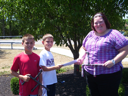 Mike Valle and Jack Dlugokinski contributed some of the profits of their sales of marshmallow shooters to the Miracle League of Grand Island and Western New York. From left, holding a marshmallow shooter, is Dlugokinski, as Valle presents a check for $115 to Miracle League's representative Kim McMahon, who is holding a pink Marshmallow Shooter made just for her.