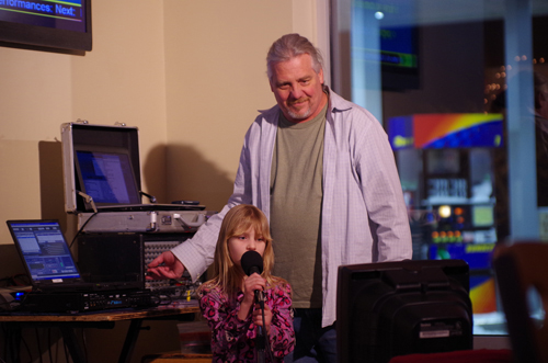John Dudley assists a young performer sing karaoke at Sunoco/Dunkin Donuts/Pizza Amoré, where Kids Karaoke runs every Thursday from 6 to 9 p.m. (photo by Larry Austin)