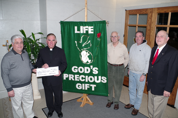 Grand Knight Sal Schiavone presents a check for $823.50 to the Rev. Paul Nogaro of St. Stephen. Also pictured are, from left, Grand Knight Dick Dietrich and Past Grand Knight Paul Minton and Financial Secretary Dan Emanuele. (Photo by Larry Austin)