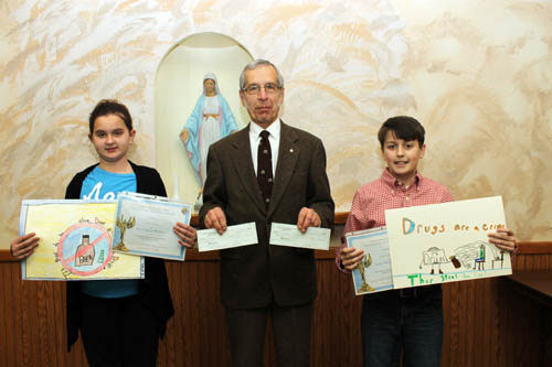 Sydney Dworak, left, of Huth Road Elementary School and Spencer Mitchell of St. Stephen School display their winning entries in the Grand Island Knights of Columbus poster contest. They flank Peter Kuszczak, poster contest chairman, who presented both students with $50 checks for winning their respective categories in the contest. (photo by Larry Austin)