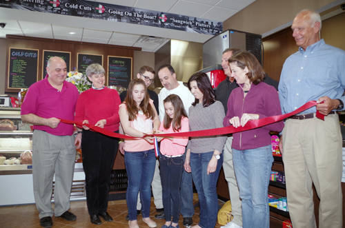Friends, family, government officials and supporters of the new Marco's Italian Deli at 1441 Ransom Road took part in a ribbon-cutting ceremony for the business on Sunday, April 6. From left, front row: Angelo Grande, Town Supervisor Mary Cooke, Maria Sciortino, Gabriella Sciortino, Vicki Sciortino, Town Clerk Pattie Frentzel, and Town Councilman Ray Billica. Back row: business partners Nick Tollar Jr. and Mark Sciortino, and Chuck Rizzo. (photo by Larry Austin)