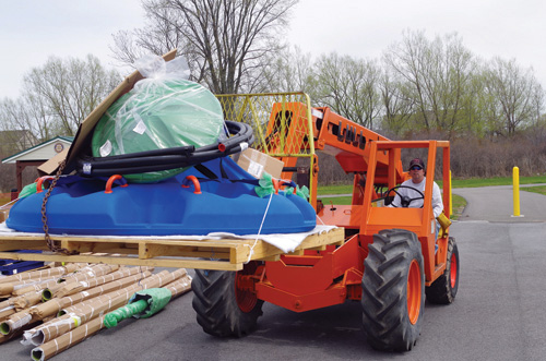 Dan Drexelius unloads playground equipment that was delivered to the Miracle League of Grand Island and Western New York Wednesday afternoon. The playground will be built in Veterans Park next to the present baseball diamond. (photo by Larry Austin)