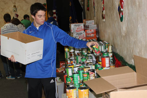 Alex Ahne of the Grand Island High School DECA club, helps sort some of the hundreds of cans of food headed for 60 needy families on the Island from the Neighbors Foundation's canned food drive. (photo by Larry Austin)