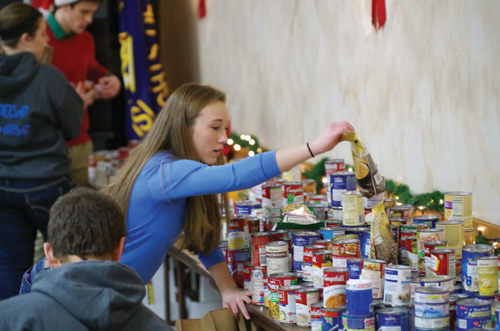 Grand Island High School student Julia Lawley sorts food donations dropped off at the Knights of Columbus Mary Star of the Sea Council No. 4752 hall. (photo by Larry Austin)