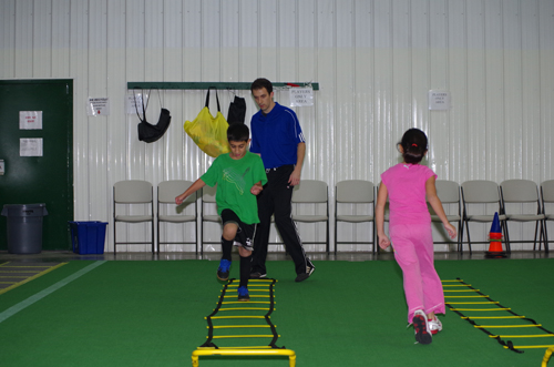 Alex Grande puts a student through his paces on the agility ladder, part of the Fit & Active Kids program at the Charging Rhinos Soccer Academy. (photo by Larry Austin)