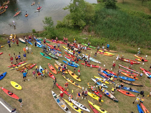 Participants in Paddles Up Niagara hoist their paddles for a pre-event photo, taken from a Grand Island Fire Co. ladder truck. (photo by Angela Berti)