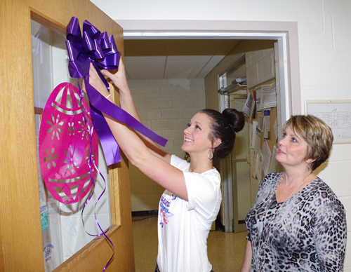 Jenna Stufkosky decorates Jacqueline McGinty's office door at Grand Island Town Hall with a purple ribbon, signifying support for the Relay For Life.