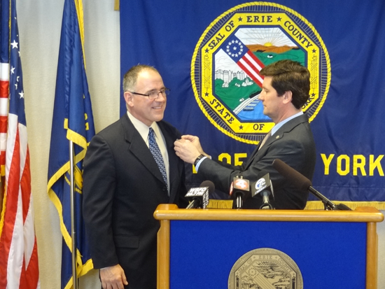 Erie County Executive Mark C. Poloncarz, right, pins an Erie County lapel pin on Al Dirschberger, the county executive's nominee for commissioner of social services.