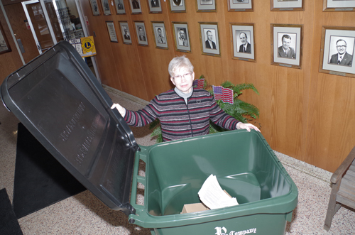 Helen Newkirk, an account clerk at Grand Island Town Hall, easily handles a new 95-gallon wheeled recycling cart. (photo by Larry Austin)