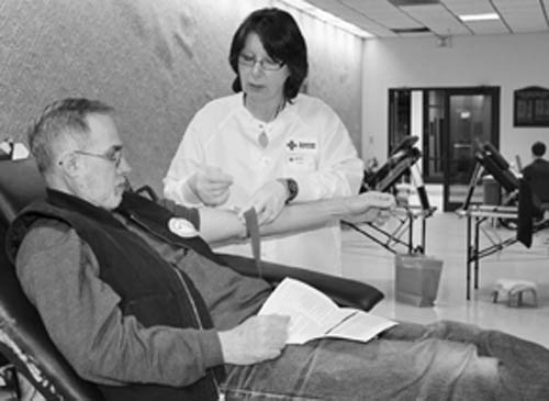 American Red Cross Donor Specialist Sandy Benjamin assists Grand Islander Bob Richards in completing his donation of blood during the Communities that Care blood drive on Dec. 27 at the Big House, Grand Island Fire Co. headquarters on Baseline Road. Richards was one of 41 blood donors on the day. (photo by Larry Austin)