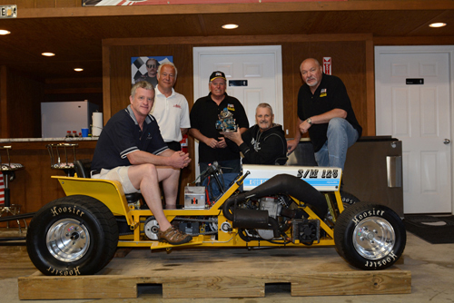 Gentlemen, start your engines. The B.A.D. Racing Team spent months building their entry in the annual Father's Day Lawn Mower Races. From left, Scot Andres on mower, Rick Greenawalt, Tom Harrison, Tom Long (holding last year's winning trophy) and Tom Snyder.