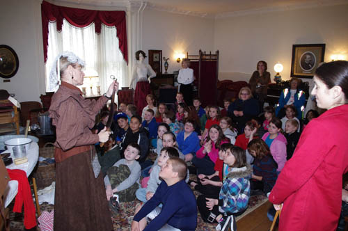 Students from Kaegebein Elementary School recently took a field trip to River Lea to learn about local history. Pictured at far left, docent Maggie Gushue shows the students a leather razor strop used mainly for polishing the blade of a man's shaving straight razor, but also, Gushue said, for corporal punishment of children. (photo by Larry Austin)
