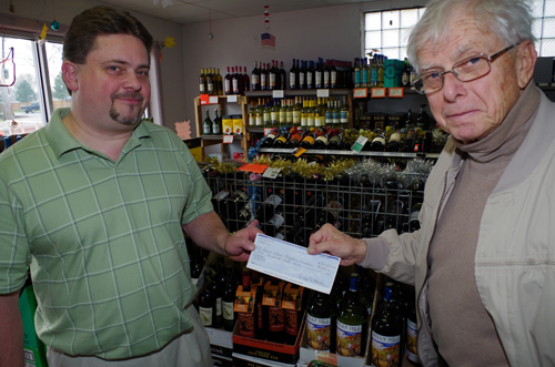 Dave Dulak, left, manager of The Rose Liquor Store, presents a check for $500 from the store and owner Michael Hachee to Henry Kammerer, president of the Neighbors Foundation of Grand Island, to support the less fortunate in the community. The store also has a Neighbors Foundation collection box for donation of non-perishable foods. (photo by Larry Austin)