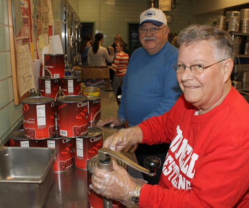 Rotarians Dr. Jared Barlow, right, and Angelo Palamuso (Grand Island Rotary treasurer) open cans of ingredients for the chili made Tuesday by the Interact Club of Grand Island High School.