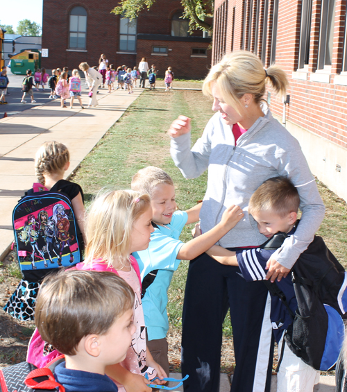 Returning students at Charlotte Sidway Elementary School and physical education teacher Kelly Greene greeted each other on the first day of school Wednesday. See more photos from the first day of school at Sidway on the Picture Page. (photo by Larry Austin)