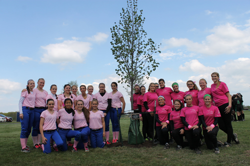 Varsity softball teams from Grand Island, left, and Lewiston-Porter meet at a tree dedicated in memory of Rosanna Russell prior to Wednesday's Strike Out Cancer game in Veterans Park. The tree honors Russell, who lost her battle with cancer three years ago. (photo by Larry Austin)
