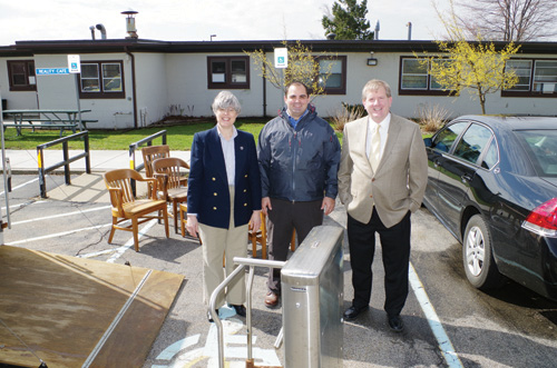 Town Supervisor Mary Cooke, Town Recreation Director Joe Menter and Erie County Legislator Kevin Hardwick stand with some of the surplus furniture delivered to the town from the county surplus warehouse Thursday, including a turnstile from Ralph Wilson Stadium, foreground. All the items came at no cost to the town. (photo by Larry Austin)